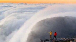 Clouds move down mountain like waterfall