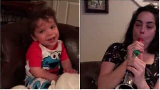 Hilarious baby can't stop laughing at mom playing the flute