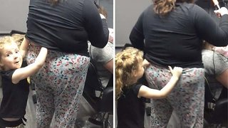 Cheeky toddler pulls her auntie's pants down while she cuts customer's hair