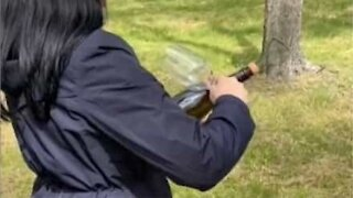 Woman uses glass to open bottle of champagne