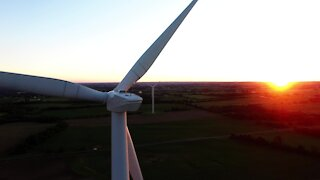 Drone accidentally records stunning sunset behind gigantic wind turbines
