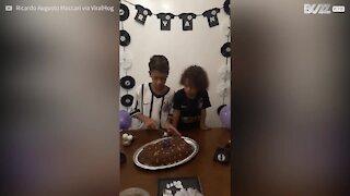 Menino emociona-se ao receber a primeira fatia de bolo do irmão