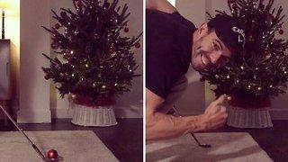 Man decorates christmas tree with golf club