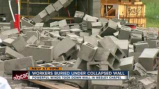 Cinder block wall collapses on construction workers taking refuge from thunderstorm