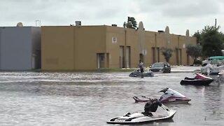 People ride jet skis through flooded Miami streets