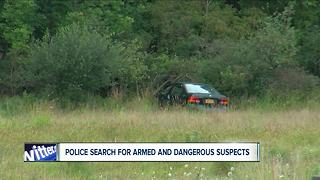 Police search for armed and dangerous suspects