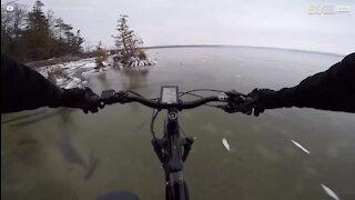 Ciclista atravessa lago gelado transparente