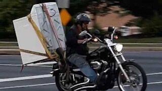Homem transporta máquina de lavar numa moto