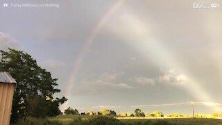 Raggi di sole, fulmini e l'arcobaleno in un unico paesaggio