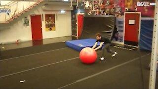 Giovane pratica incredibili acrobazie con una palla da ginnastica