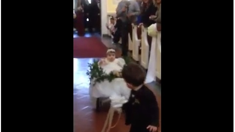 Ring Bearer Pulls Flower Girl Down The Aisle In Wedding Wagon