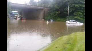 Cyclist rides through flooded road
