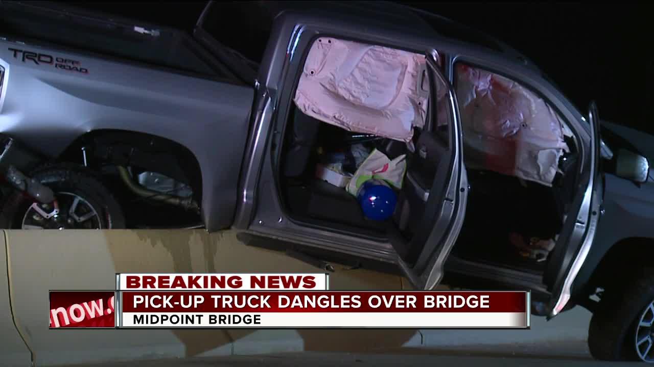 Pick-up truck dangles over bridge
