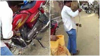 Mann trekker en slange ut av en motorsykkel