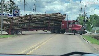 Truck jackknifes and spills logs across highway