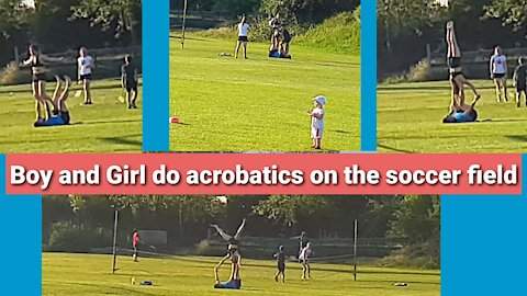 Boy and girl do acrobatics on the soccer field