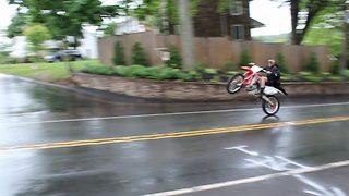 Graduate performs tricks on his bike