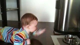 Baby 'swims' across floor to reach cat food bowl