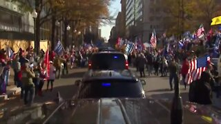 Trump thrills protesting supporters with motorcade drive-by