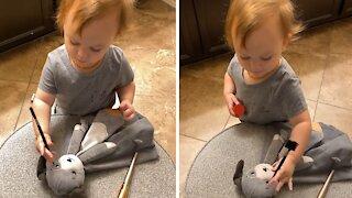 Precious toddler adorably applies makeup to stuffed animal