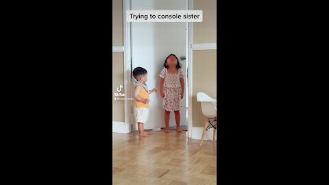 Baby boy tries to console crying sister