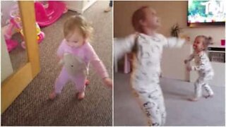 Girl helps her sick little sister take her first steps