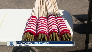 Volunteers place flags on gravestones for Memorial Day