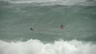 Heavy rain and active waves for surfers at Lake Worth Beach