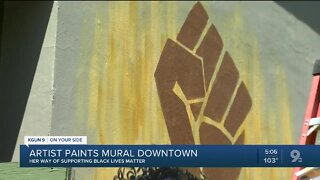 Artist paints mural downtown