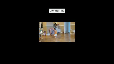 Baby boy and sister play dinosaur