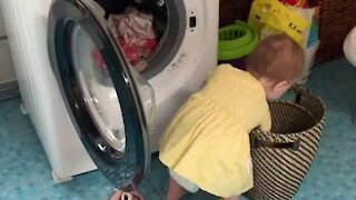 Baby adorably helps her mom with the laundry