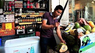 Skilled coconut vendor in Playa Del Carmen street impresses Canadian tourists
