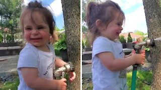 Toddler hilariously tries to catch water from garden hose