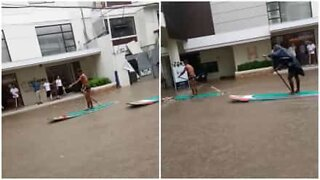Innbyggere på padlebrett gjennom oversvømte gater på Filippinene