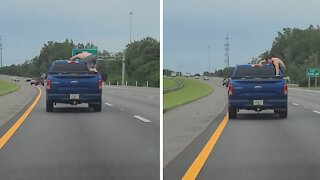 Man climbs out of truck on highway to grab beer from the back