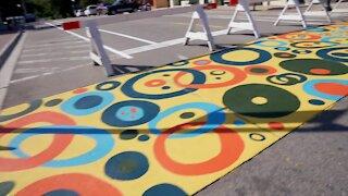 DeWitt volunteers paint crosswalks with local artist