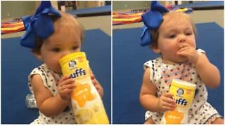 Baby doesn't need any help from parents to finish favorite snack