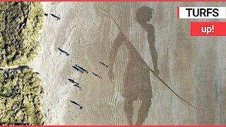 Artist creates 150ft sketch of a giant surfer on sand using a garden rake