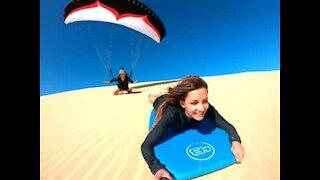 Parapente contre sandboard, la course parmi les dunes