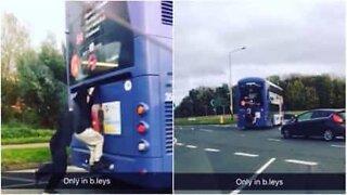 Attention, danger! Ces jeunes s'accrochent à l'arrière d'un bus.