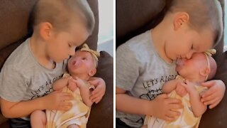 Big brother sweetly cuddles his new baby sister