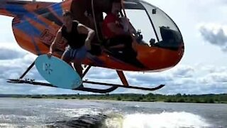 Surfer jumps from helicopter with his board