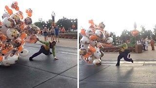 BRAVE DISNEY WORKER STRUGGLES TO HOLD ON TO BALLOONS AS STRONG WINDS HIT PARK