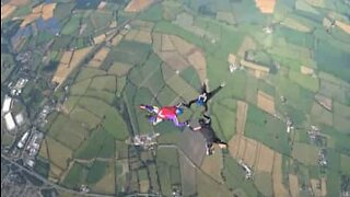 Friends hold onto each other while skydiving