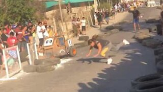 Woman running across race track stumbles over tire