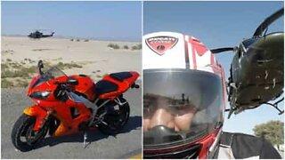 Motorsyklisten kjører fort under lavflygende helikopter