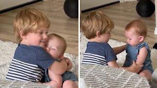 Big brother preciously hugs his baby sister