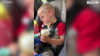 Menino dorme tomando sorvete