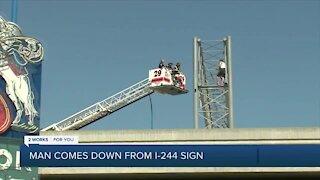 Negotiators talk man down from I-244 sign