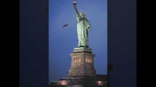 ufo passes by the statue of liberty